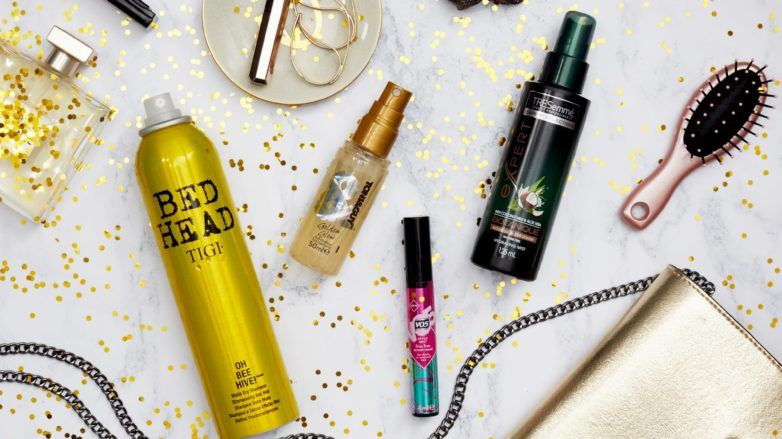 Party hair products: Flat lay of Tigi Bedhead, Toni & Guy, VO5 and TRESemmé products against a white background with golden glitter on it, with gold handbag and hair brush, hair scrunchie