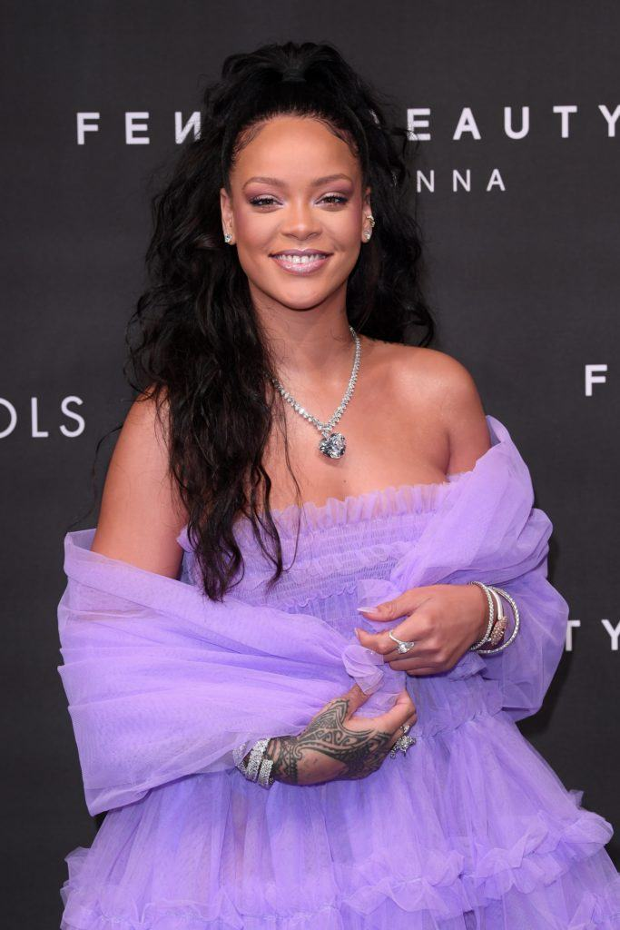 close up shot of rihanna with half up ponytail and curly hair, wearing purple dress and necklace at the fenty beauty launch