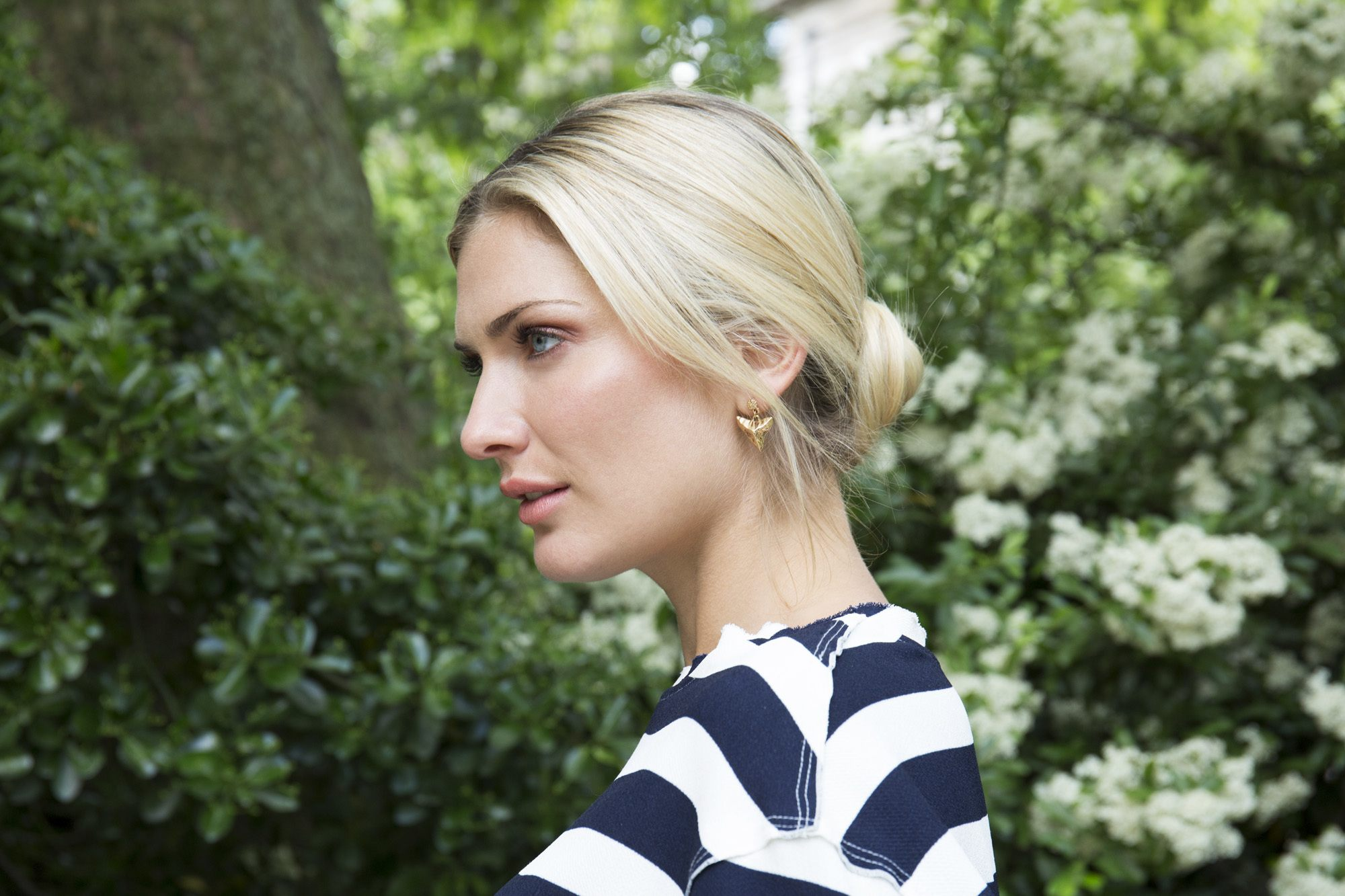 low bun hairstyles: close up shot of model with sleek, romantic low bun updo hairstyle, posing outside and wearing striped top