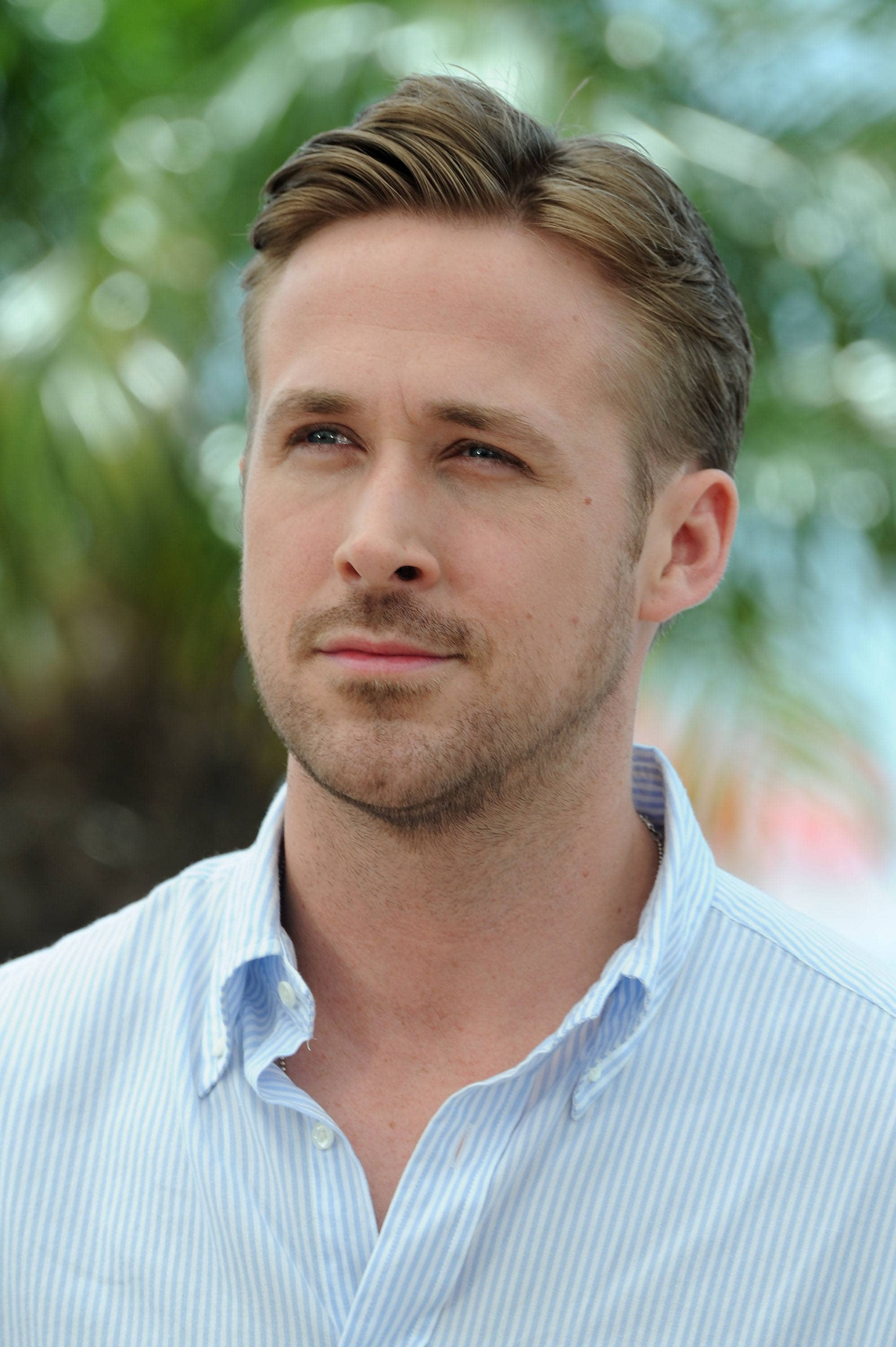 Ryan Gosling haircut: Ryan Gosling with a mid-length combover with short tapered sides, wearing a blue shirt