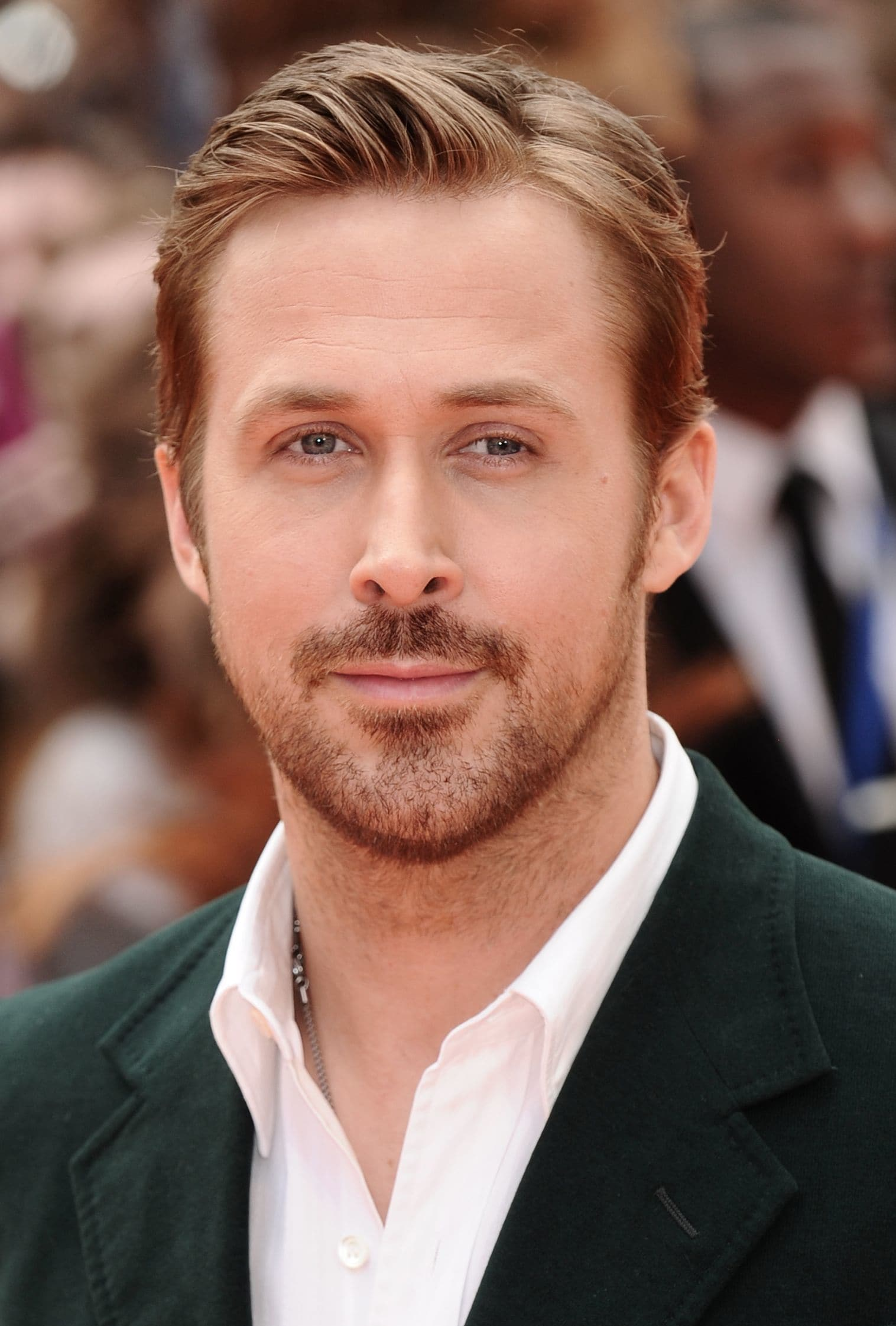 Ryan Gosling haircut: Ryan Gosling with a comb over haircut and facial hair, wearing a green suit