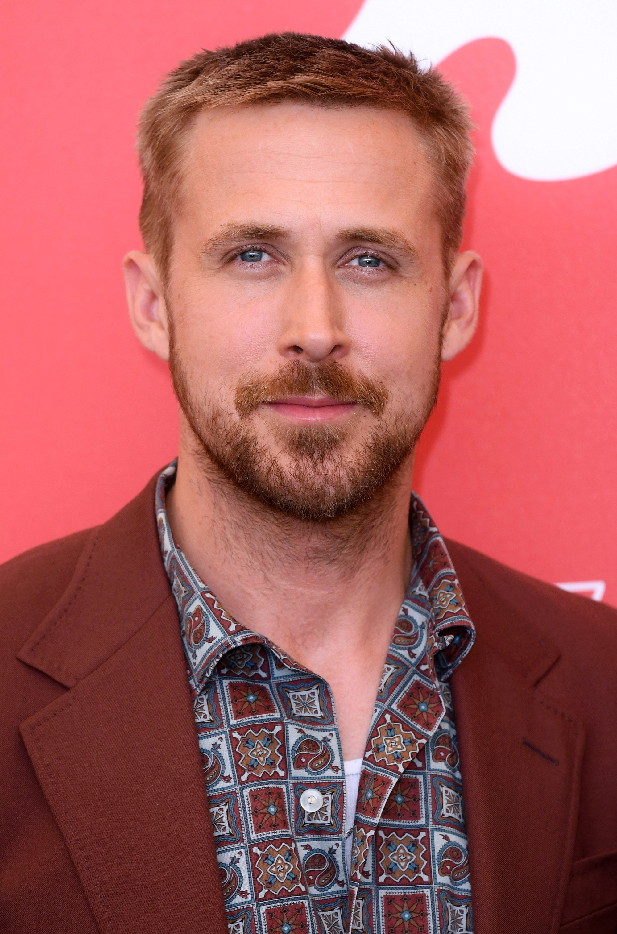 Ryan Gosling haircut: Ryan Gosling with a short classic crew cut with facial hair, wearing a patterned shirt and brown blazer