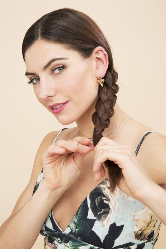 Side plait tutorial girl looking at camera and tying her braid