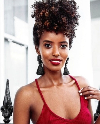 woman wearing a red top with her natural hair in a pineapple updo style with statement tassel earrings
