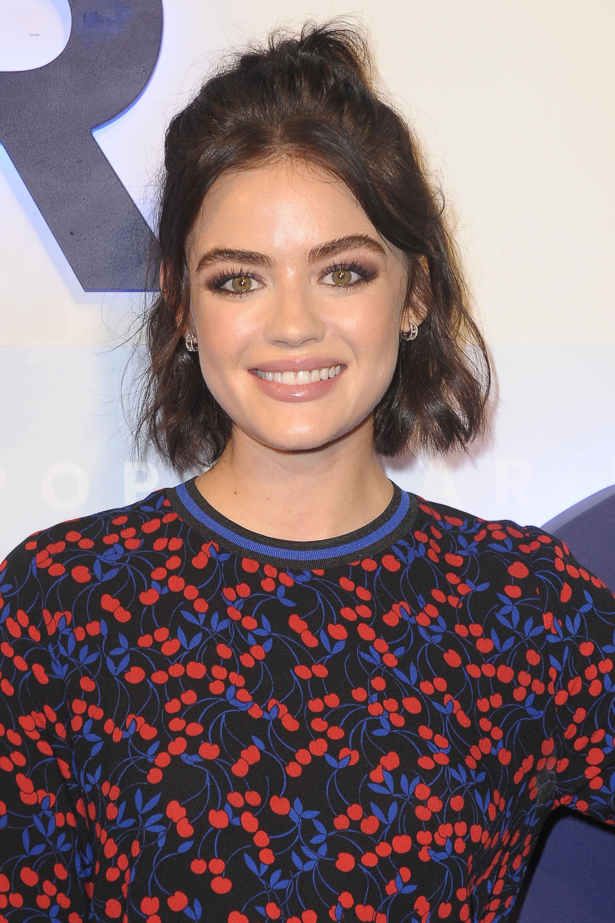 Lucy Hale with her dark brown hair styled into a tousled half-up, half-down bun hairstyle, wearing printed jumper on the red carpet