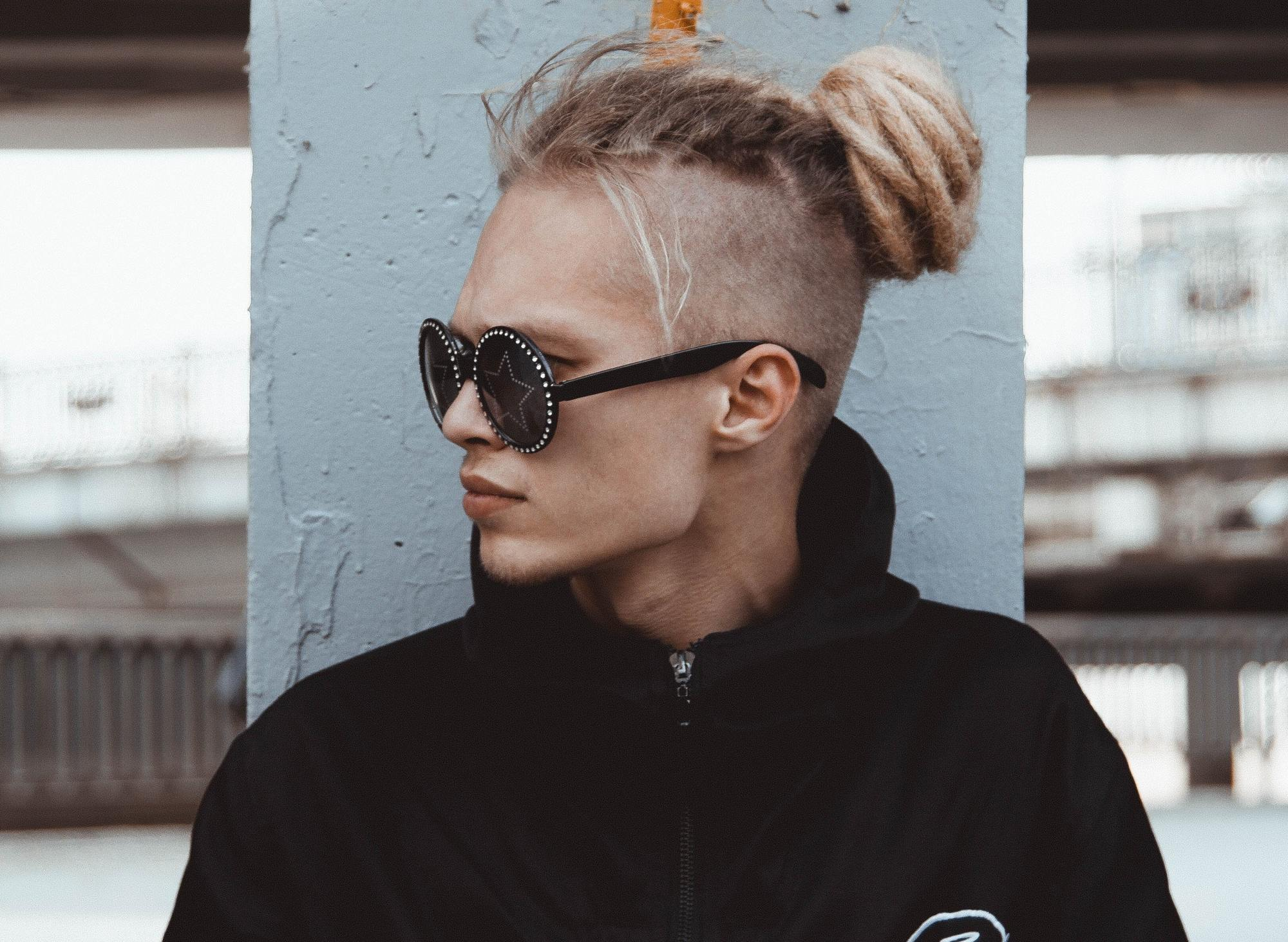 Man with long undercut and blonde dreads styled into a bun