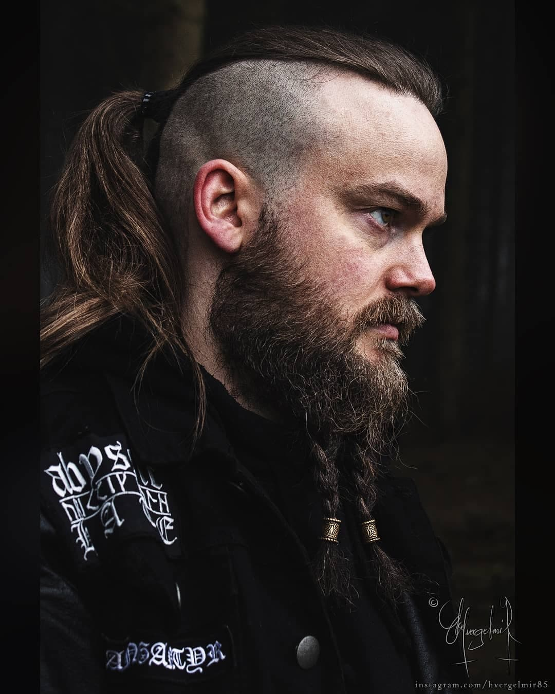 Man with disconnected undercut haircut with long hair styled into a ponytail and beard