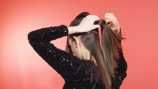 Brunette girl tying a ponytail into a hairband
