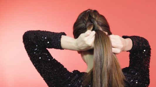 Brunette girl tying hair into a braid