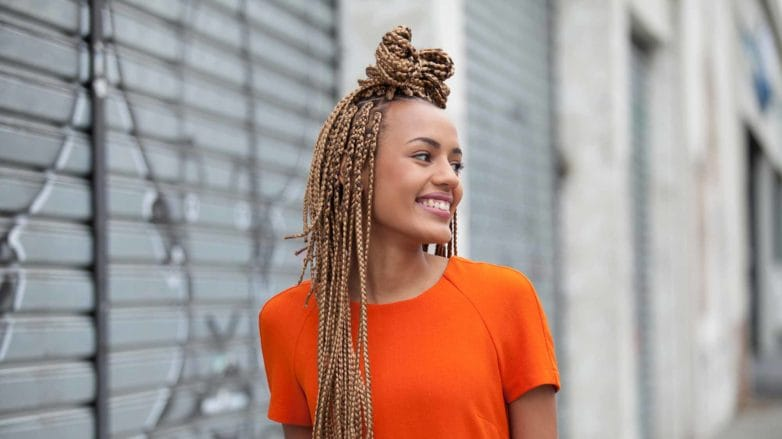 How long do box braids last woman with box braids standing in street