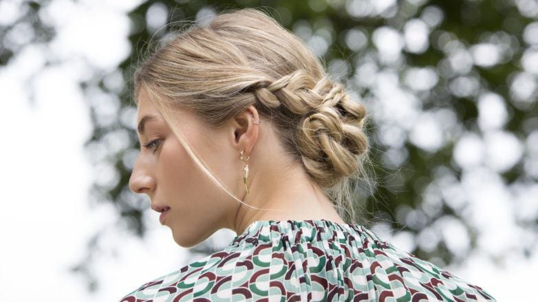 a braided chignon of a woman rear view standing outside