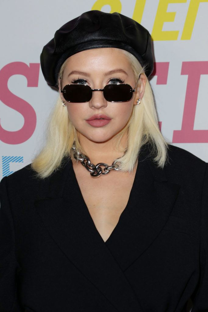 singer christina aguilera with a platinum lob and black beret hat