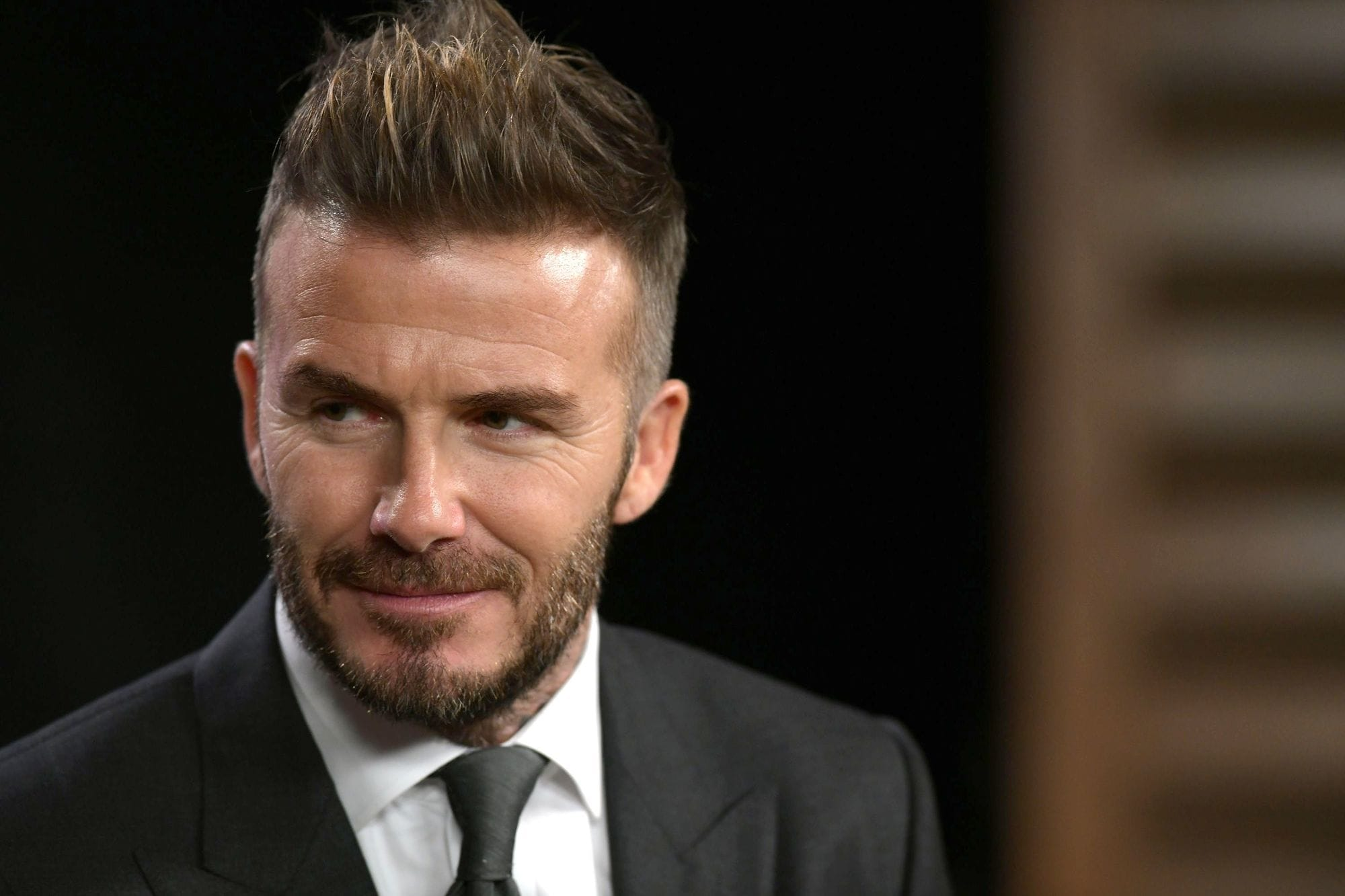 close up shot of david beckham with new swept back quiff and low fade haircut, with neat beard, wearing suit