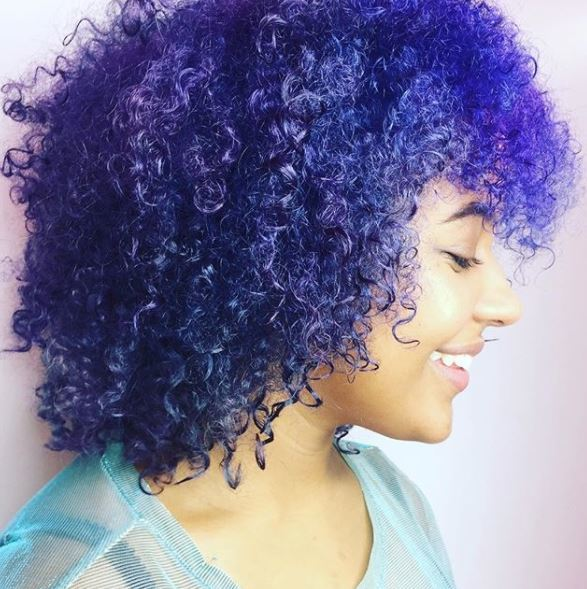 side view of purple curly shoulder length hair with curly fringe