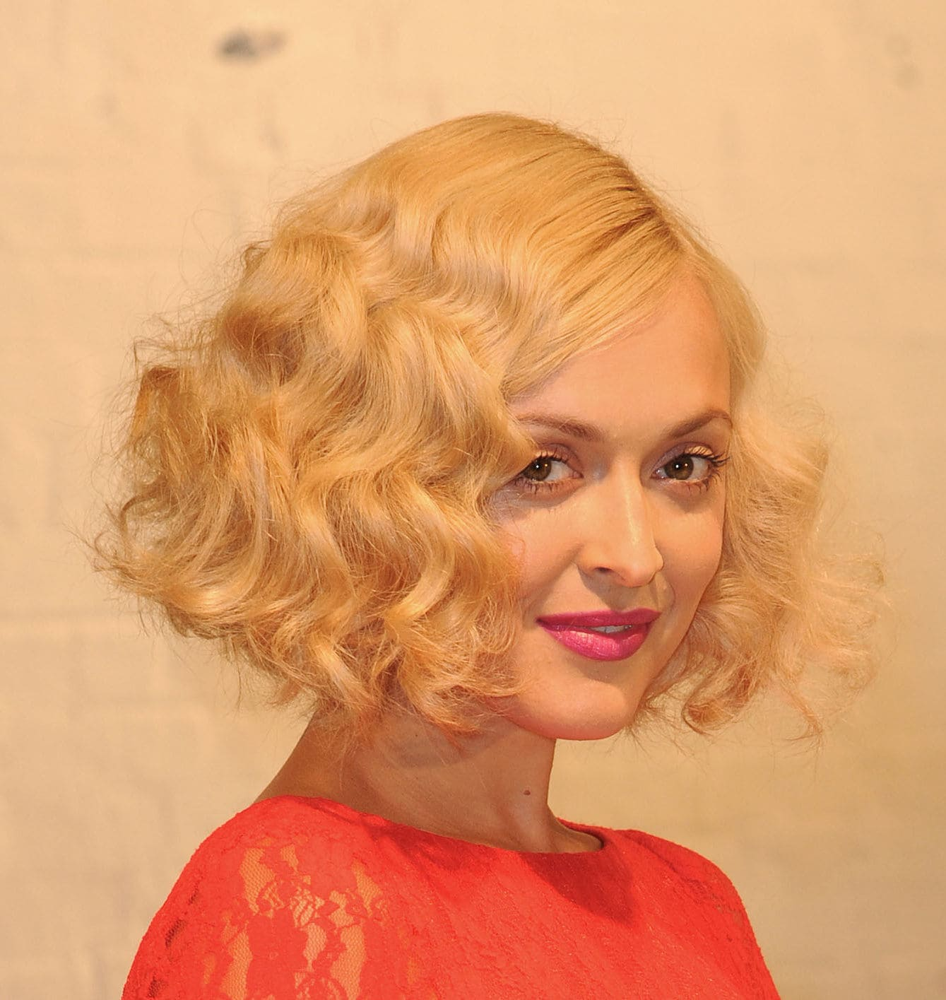 Angled bob: Fearne Cotton with a blonde 1920s inspired wavy angled bob with a side parting, wearing pink lipstick and a red lace dress