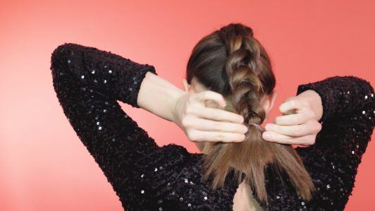 Girl with brunette hair tying a pull-through braid