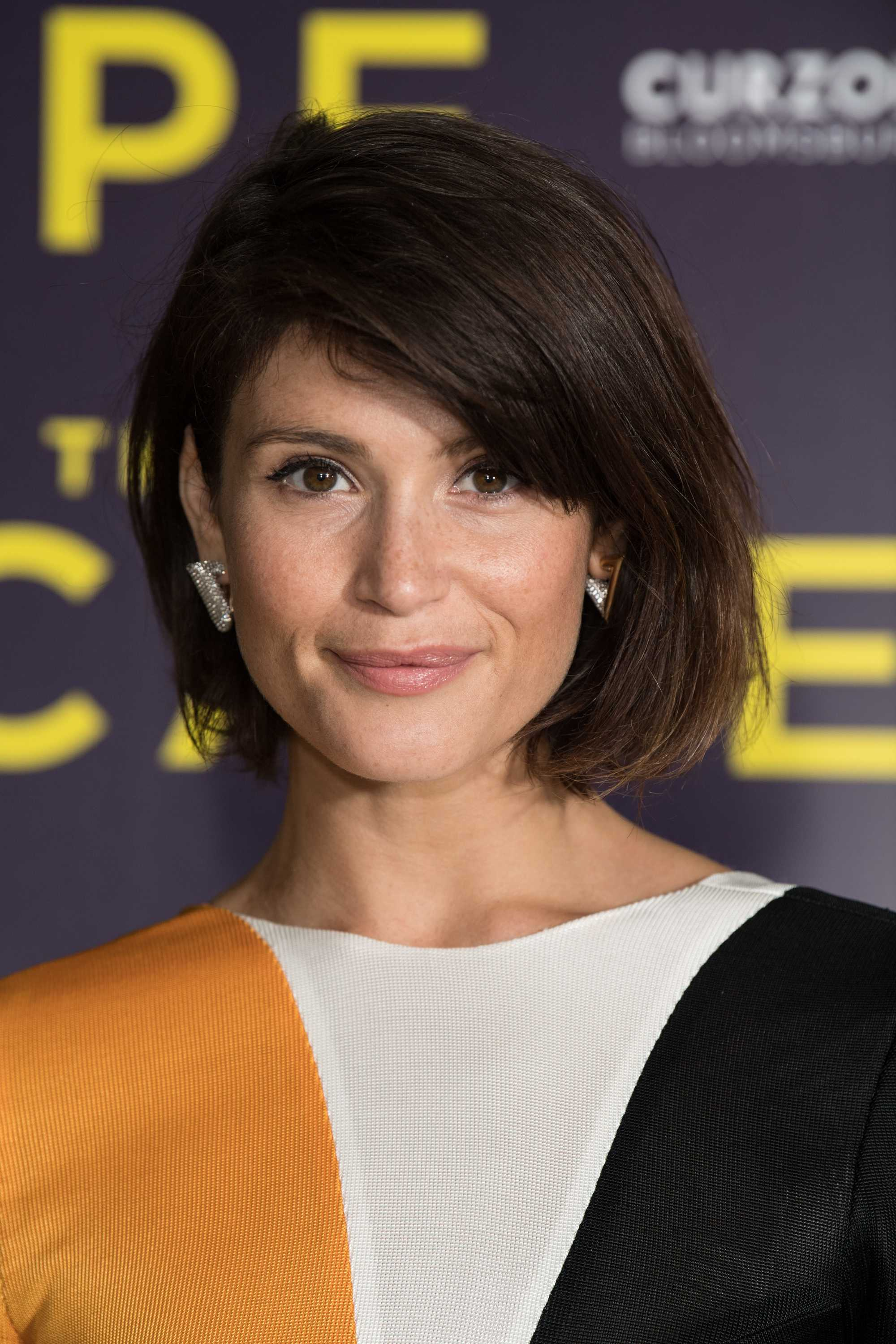 Bob hairstyles for fine hair: Gemma Arterton on the red carpet with dark brown side-swept graduated bob, wearing printed top