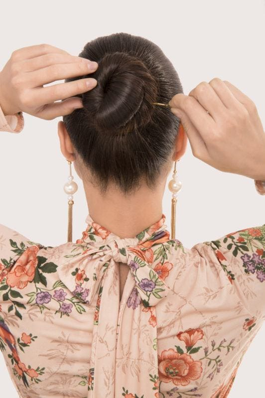 Ballerina bun tutorial brunette girl pinning bun into place with back to camera