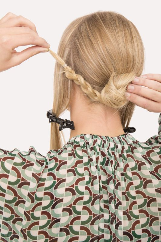 Braided updo blonde girl putting hair into a bun with back to camera