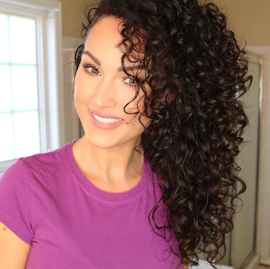 Hair plopping brunette girl smiling with voluminous curly hair