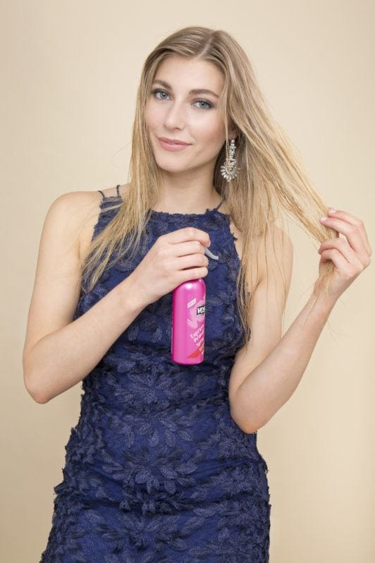a beautiful woman applying hairspray on the long blonde hair