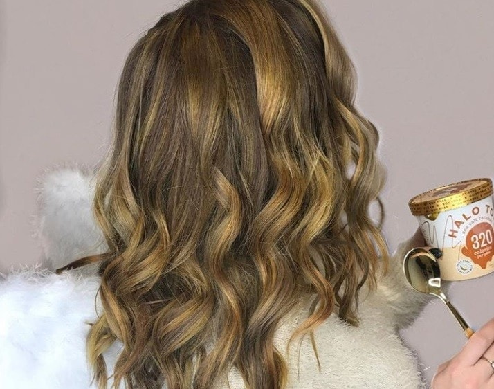 latest hair colour trends: close up shot of woman with halo top sea salt caramel hair, holding spoon and posing outside