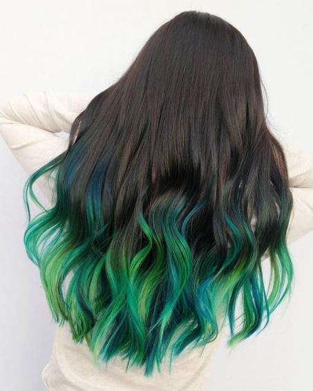 back view of woman with long wavy dark green ombre hair