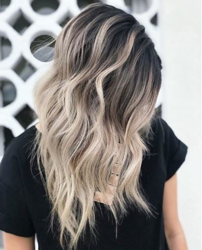 side view of woman with medium length wavy dark brown to blonde ombre