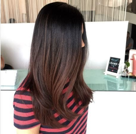 side view of woman with long dark brown ombre hair