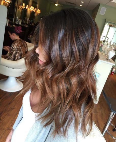 side view of woman with dark brown wavy medium length ombre hair