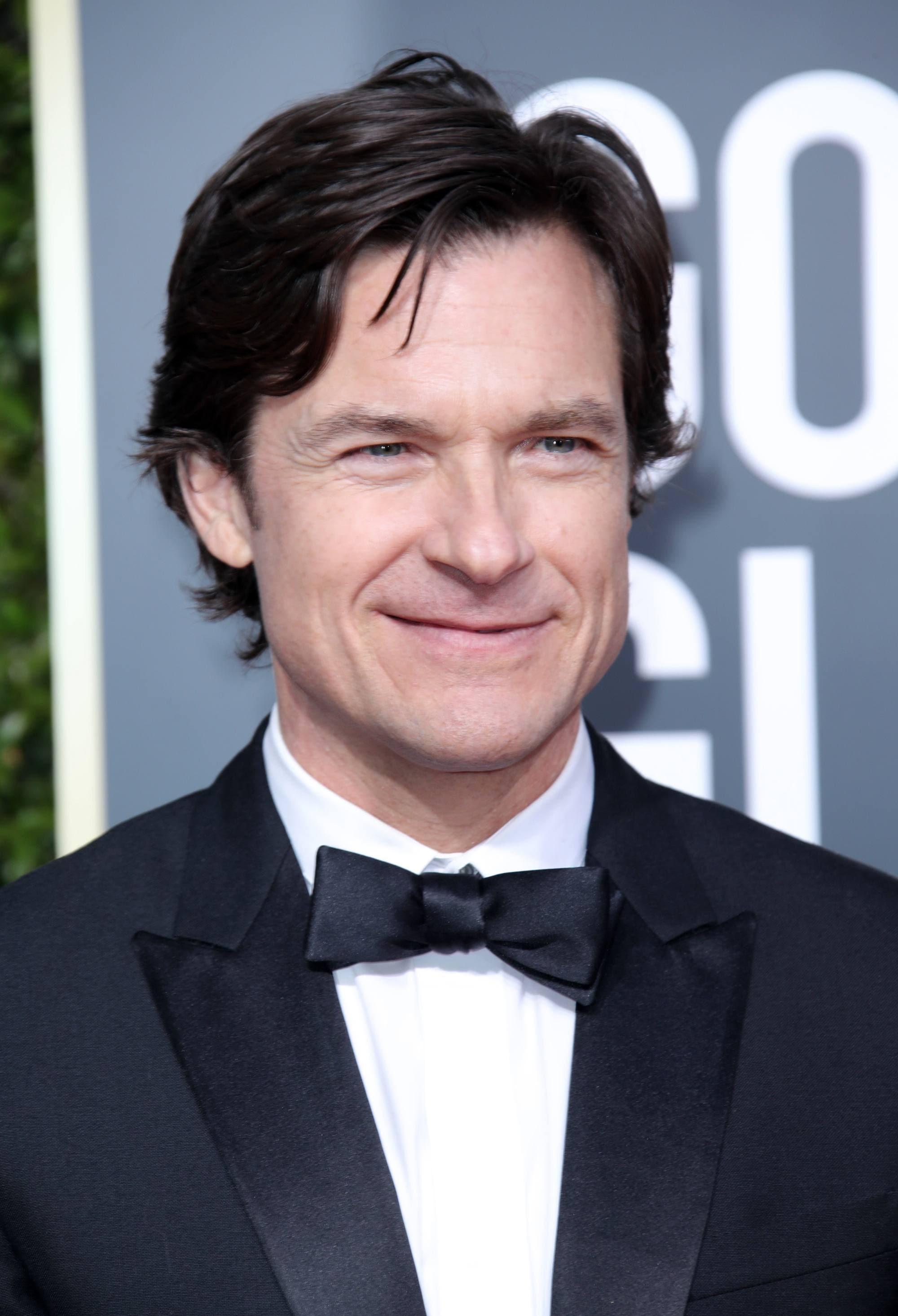 Golden Globes 2019: Close-up headshot of Jason Bateman with dark bro flow hair, wearing a tux and bow tie