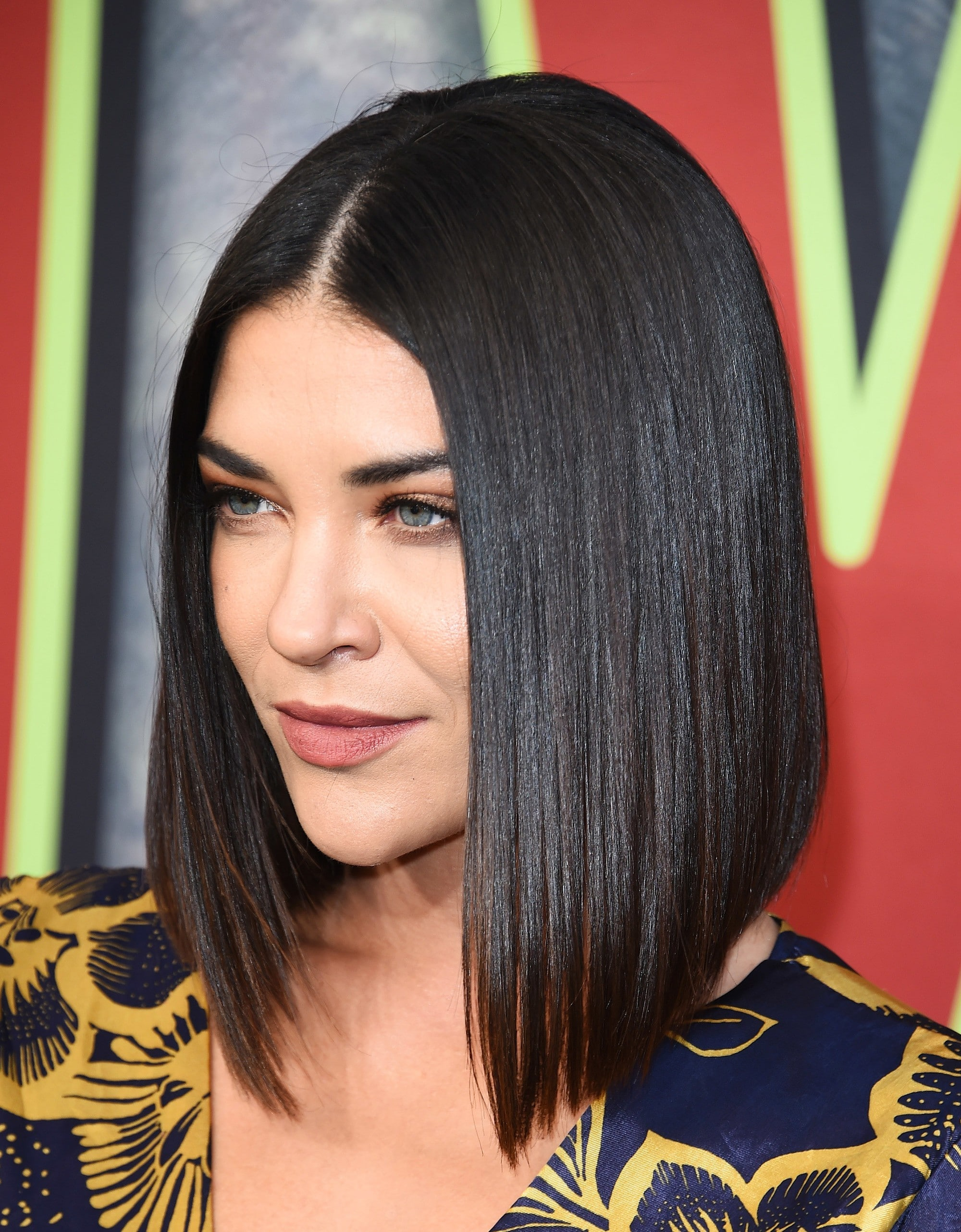 Angled bob: Close-up of Jessica Szohr with a dark brunette sharp angled bob, wearing a blue and yellow print dress