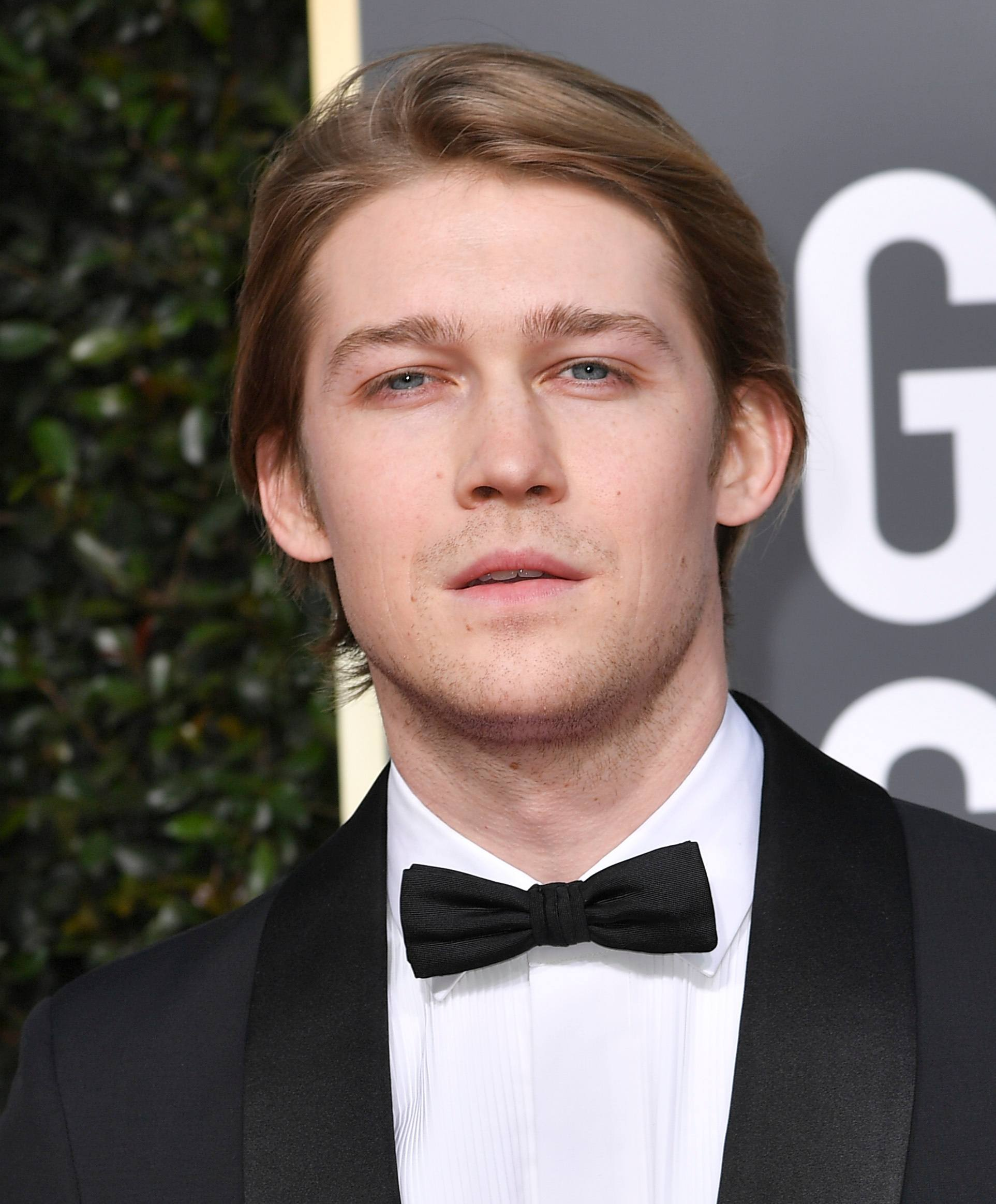 Golden Globes 2019: Close-up of Joe Alwyn with dark blonde medium length hair tucked behind his ears