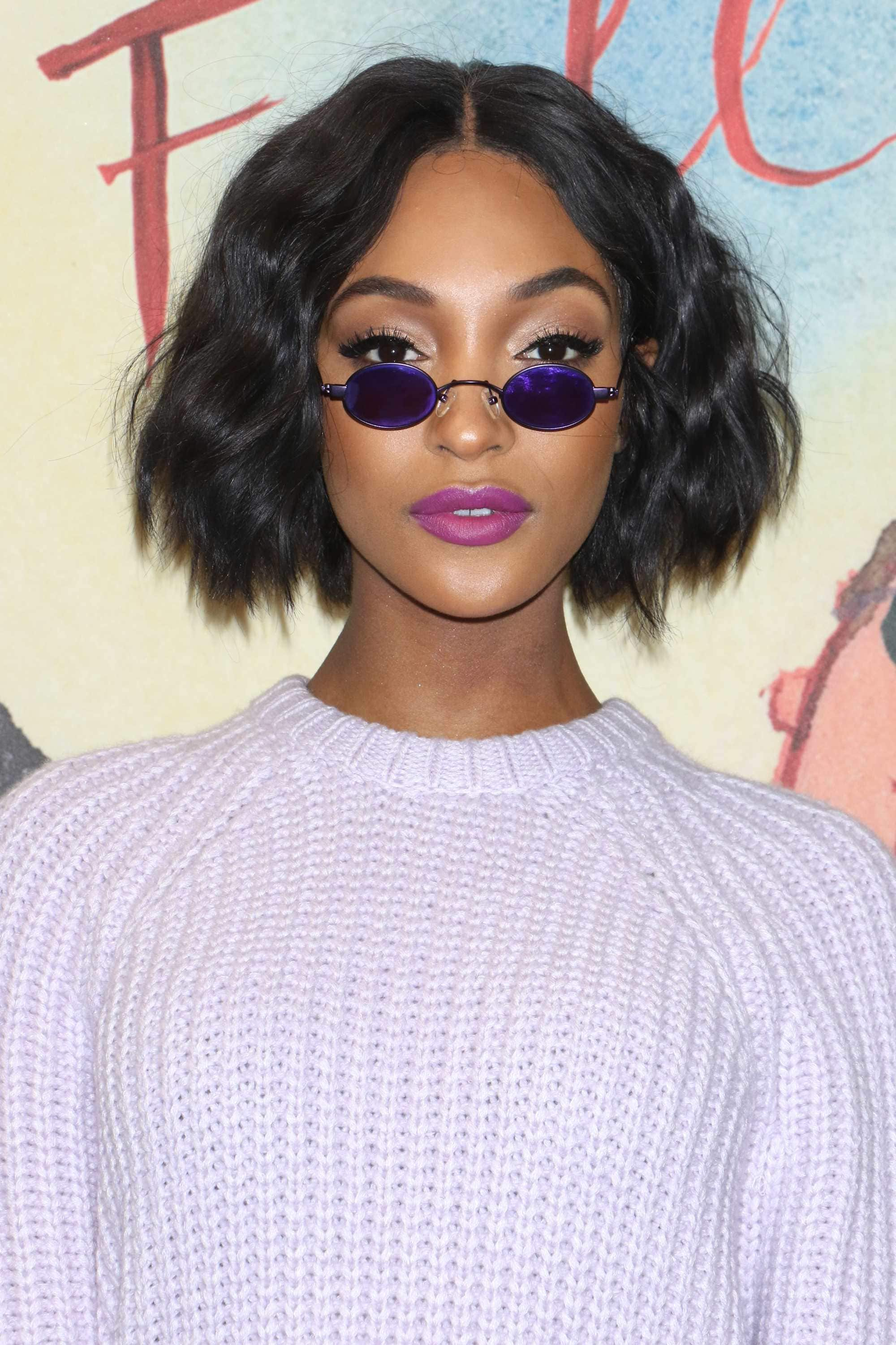 Jourdan Dunn with a wavy dark brown bob hairstyle on the red carpet, wearing a lilac jumper on the red carpet