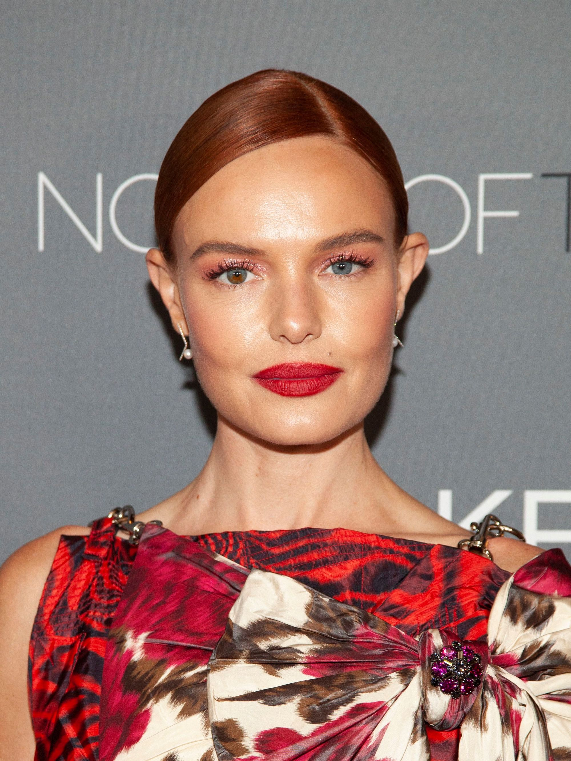 Hair trends 2019: Kate Bosworth with copper hair styled in a smooth low bun with a side parting wearing a red pattern dress and red lipstick.