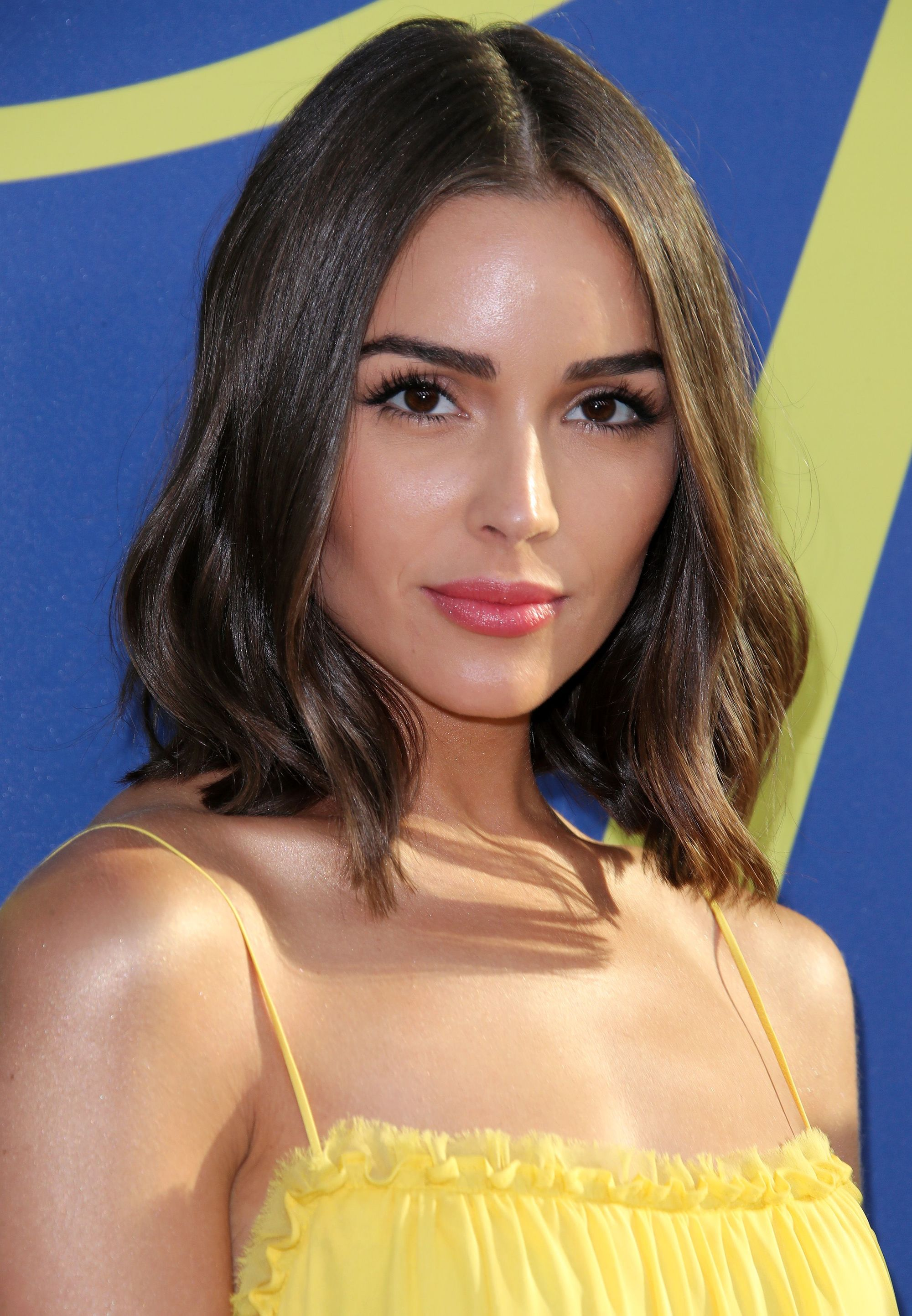 Olivia Culpo on the red carpet with long bob cut length chestnut wavy hair, wearing a yellow top