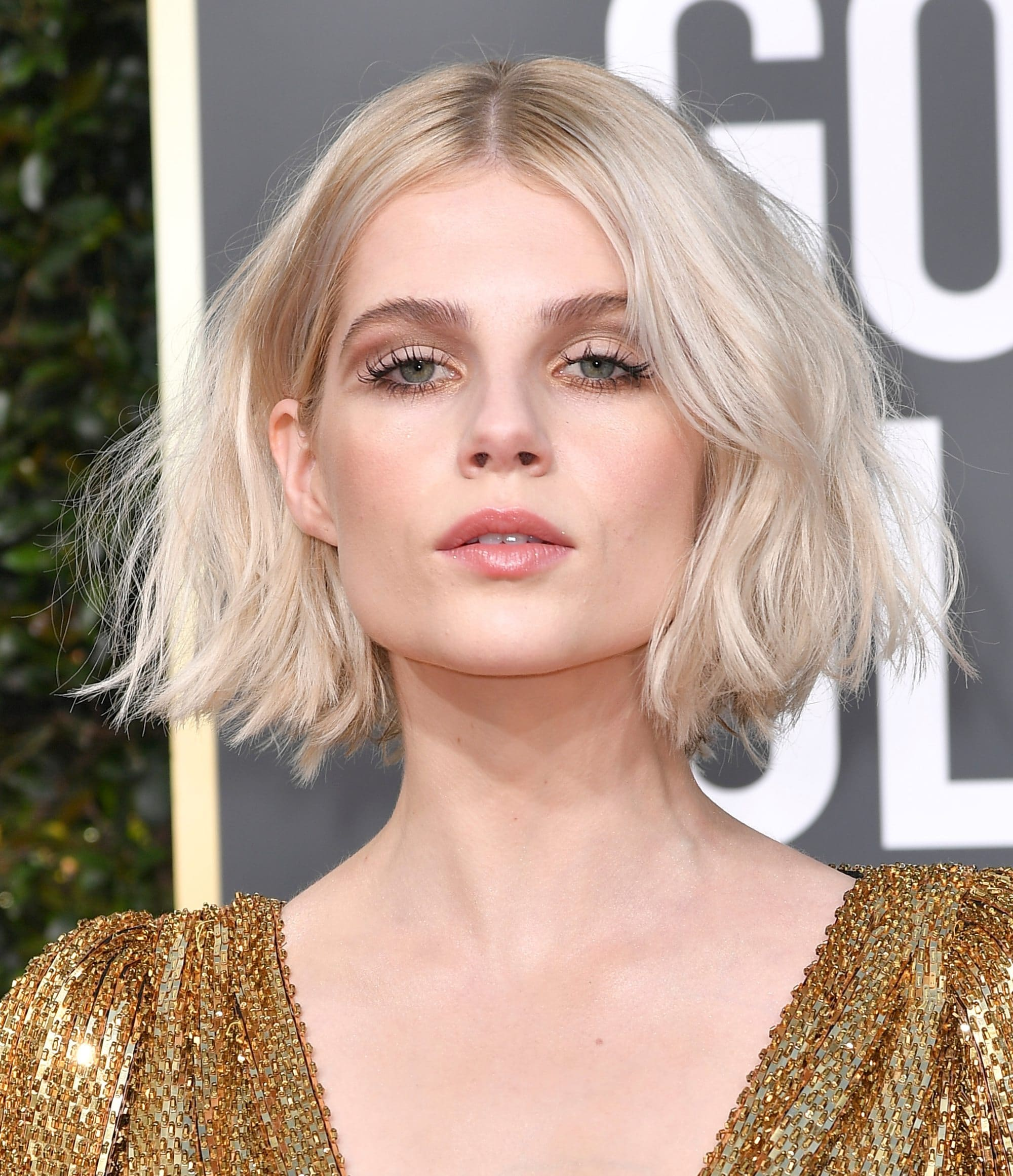 Lucy Boynton with a platinum wavy, beachy bob, wearing a gold dress on the Golden Globes