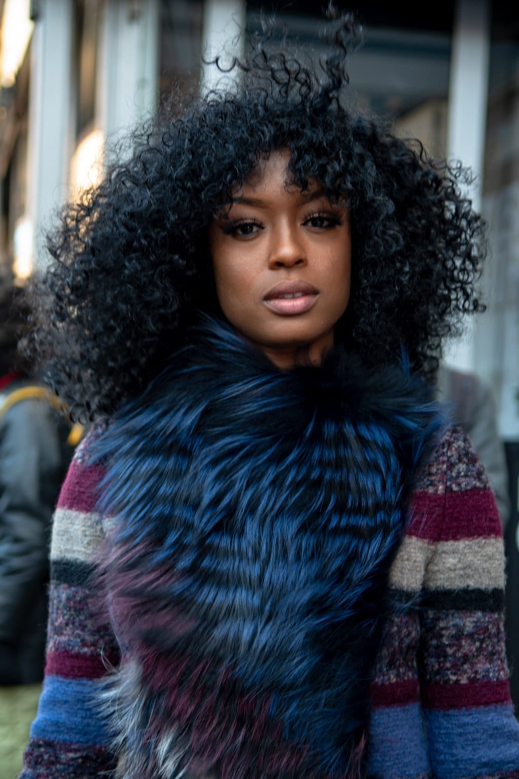 Hair trends 2019: Street style of woman with natural curly shoulder length hair with a curly fringe.
