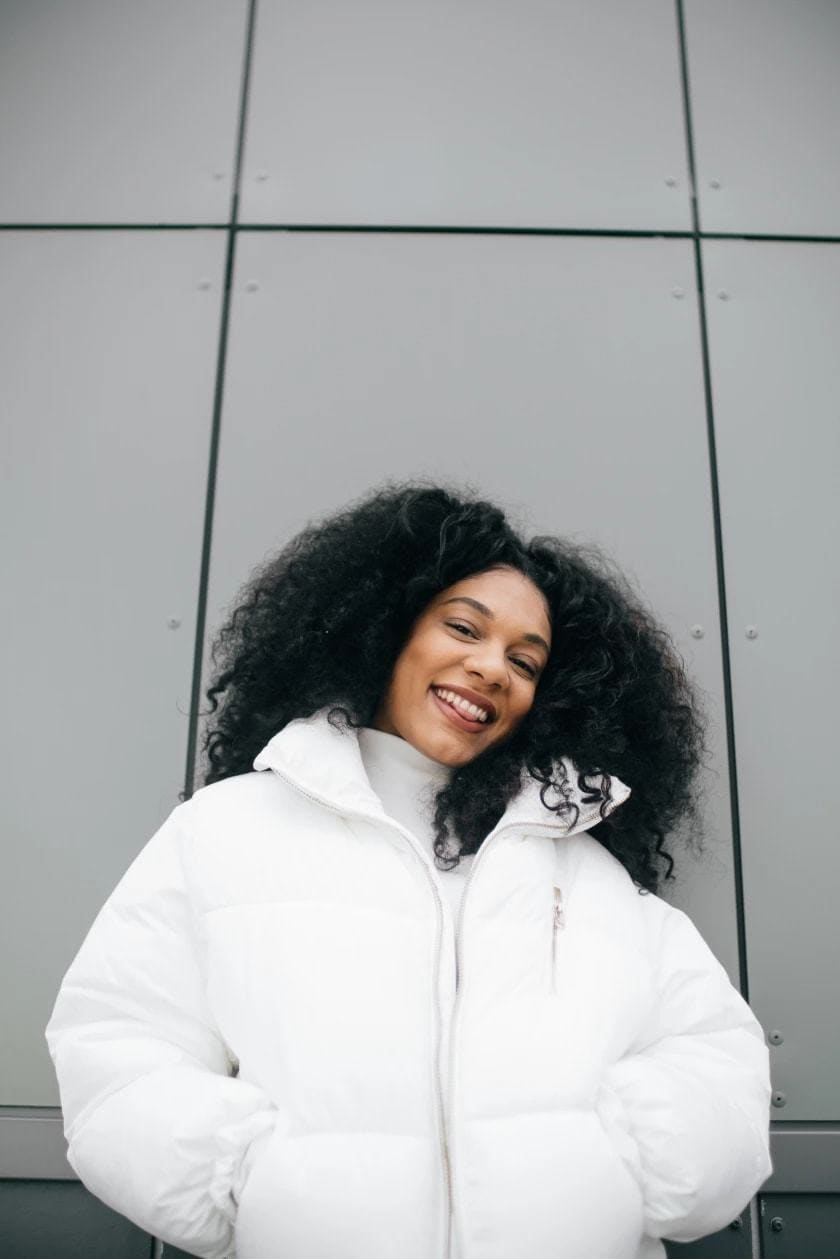 one to watch 2018 rachel foxx dark brown curly natural hair with large white puffa jacket smiling at the camera