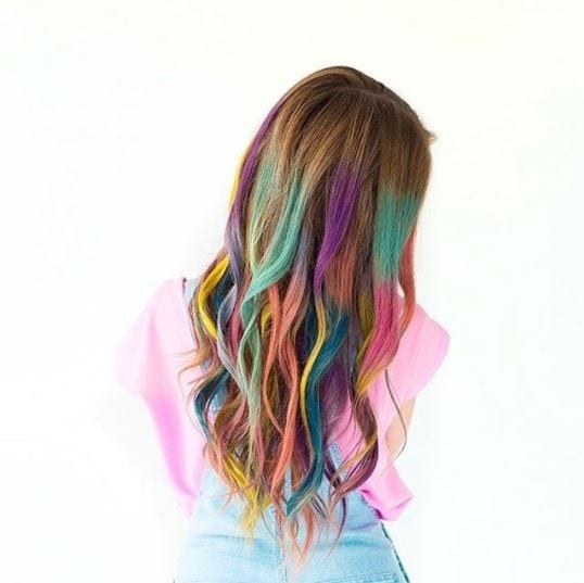 woman with light brown hair and rainbow colours added throughout her lengths