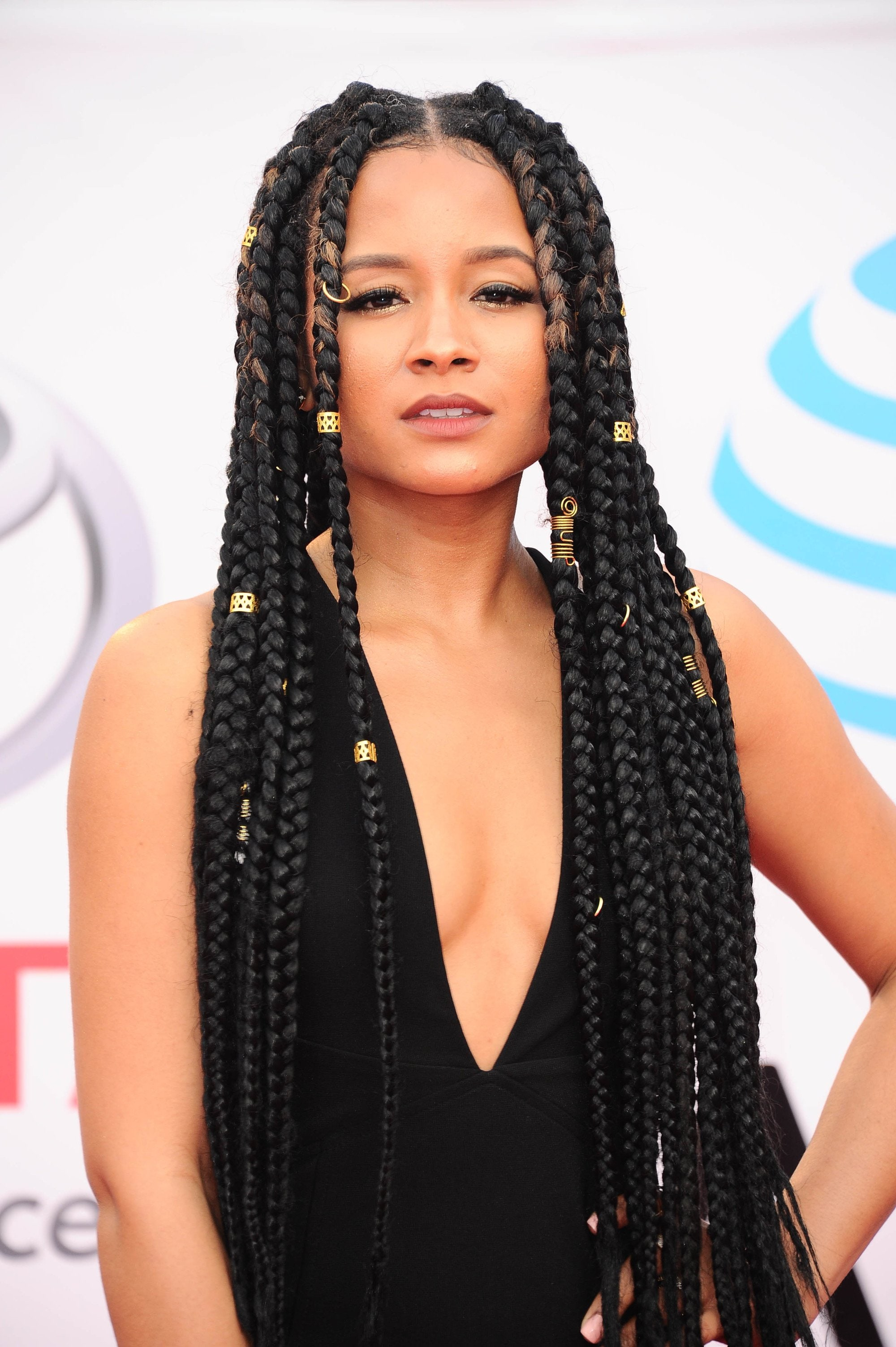 close up shot of rhyon nicole brown with long rapunzel box braids, wearing all black and posing on the naacp image awards red carpet