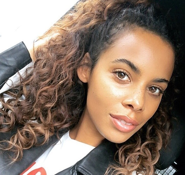 close up shot of rochelle humes with natural curly hair styled into a half up half down ponytail, wearing black jacket and posing