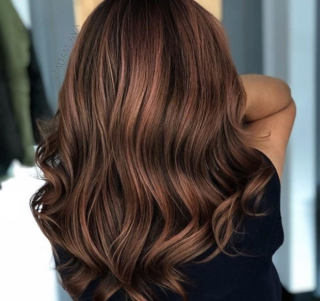 close up back shot of woman in a salon with brunette hair that has a rose tint to it, wearing all black