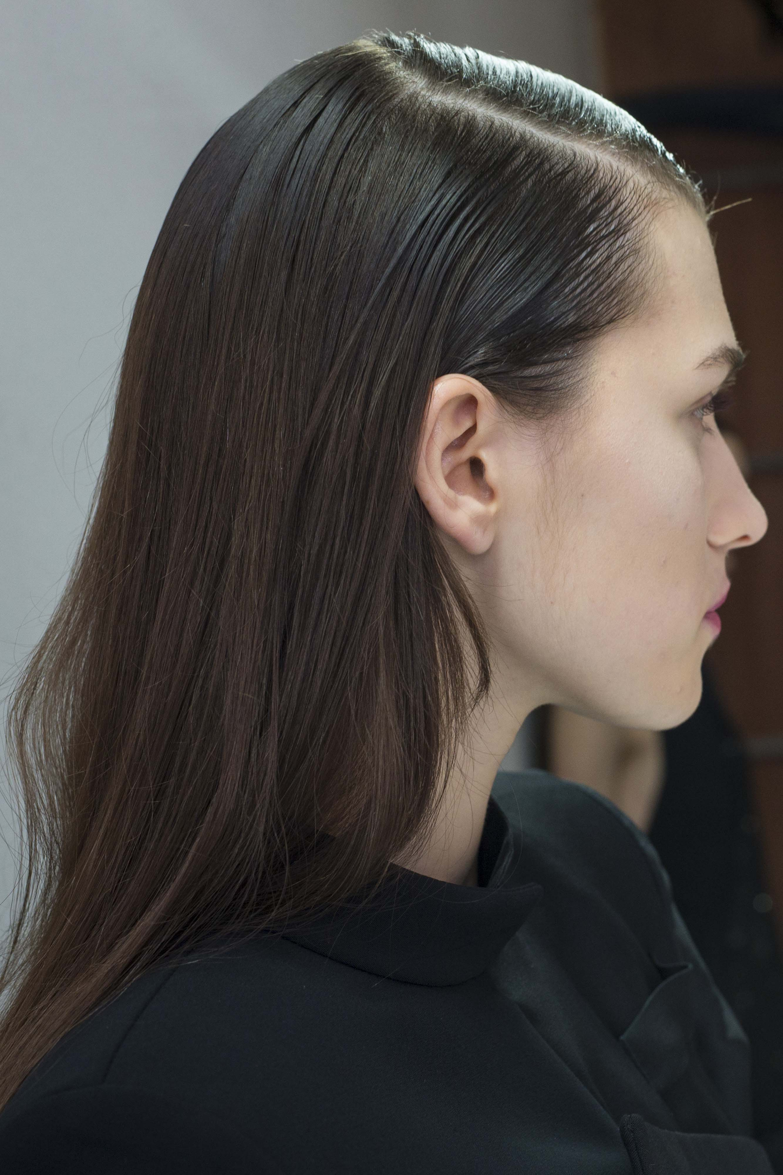 What is dandruff? Girl with brunette hair profile shot with deep side parting