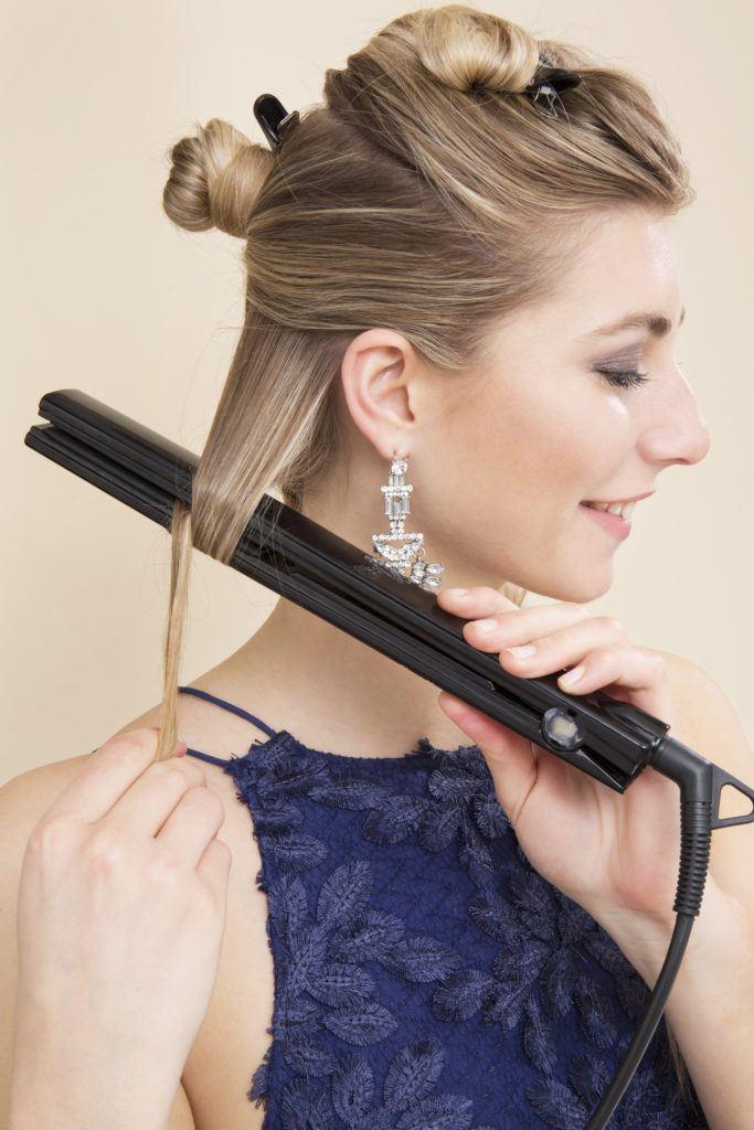 Comment boucler les cheveux avec une fille blonde en fer plat à l'aide de lisseurs