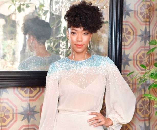 close up shot of Sonequa Martin-Green with pineapple hairstyle, wearing white see through dress and posing at an event