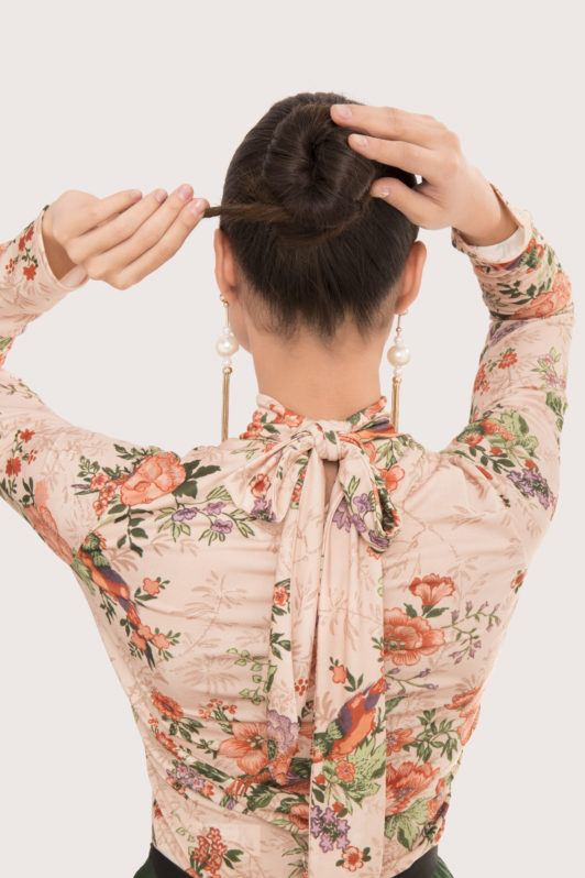 Ballerina bun tutorial brunette girl with back to the camera twisting hair into bun