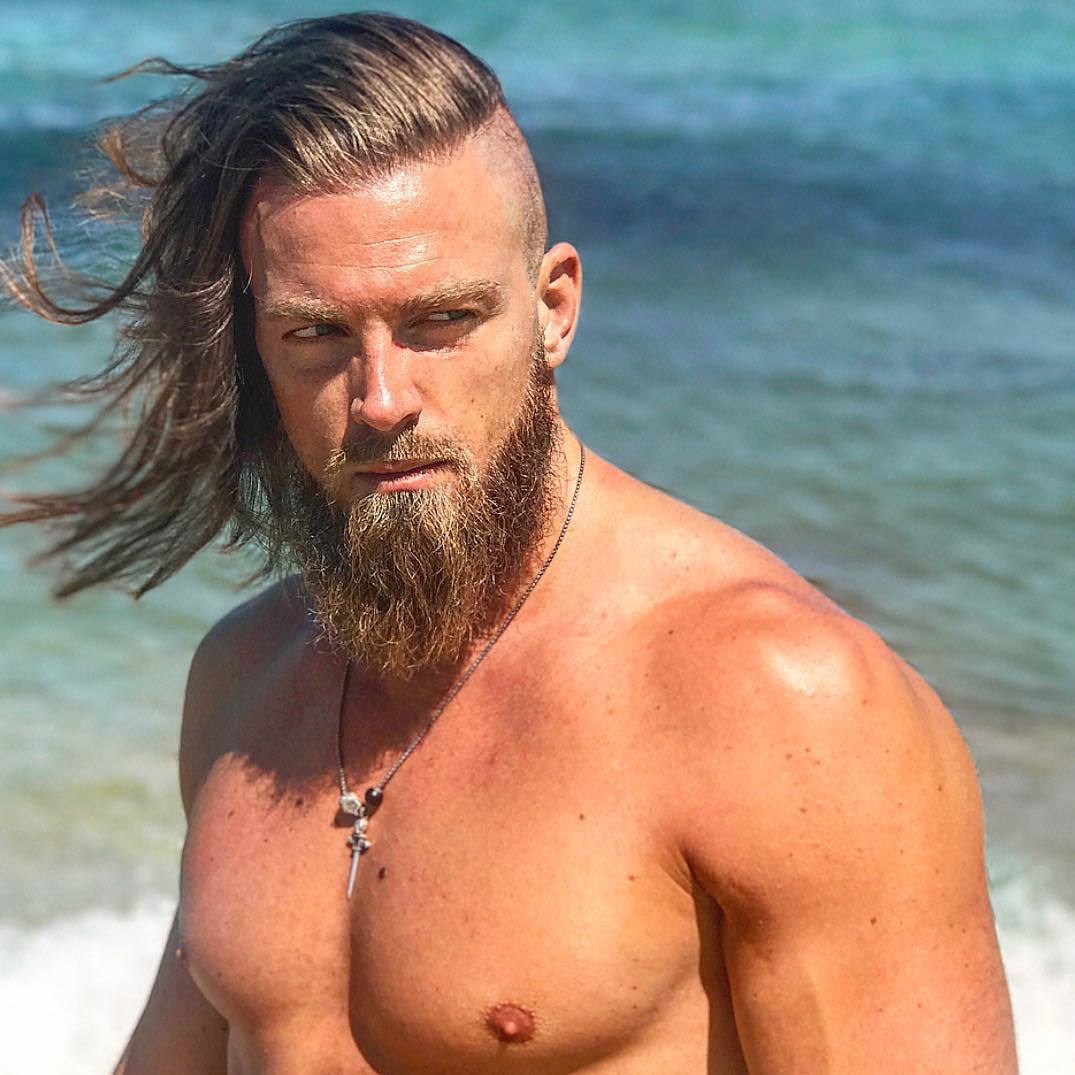 Viking Hairstyles: Man with rugged light brown hair with undercut and messy beard, wearing necklace