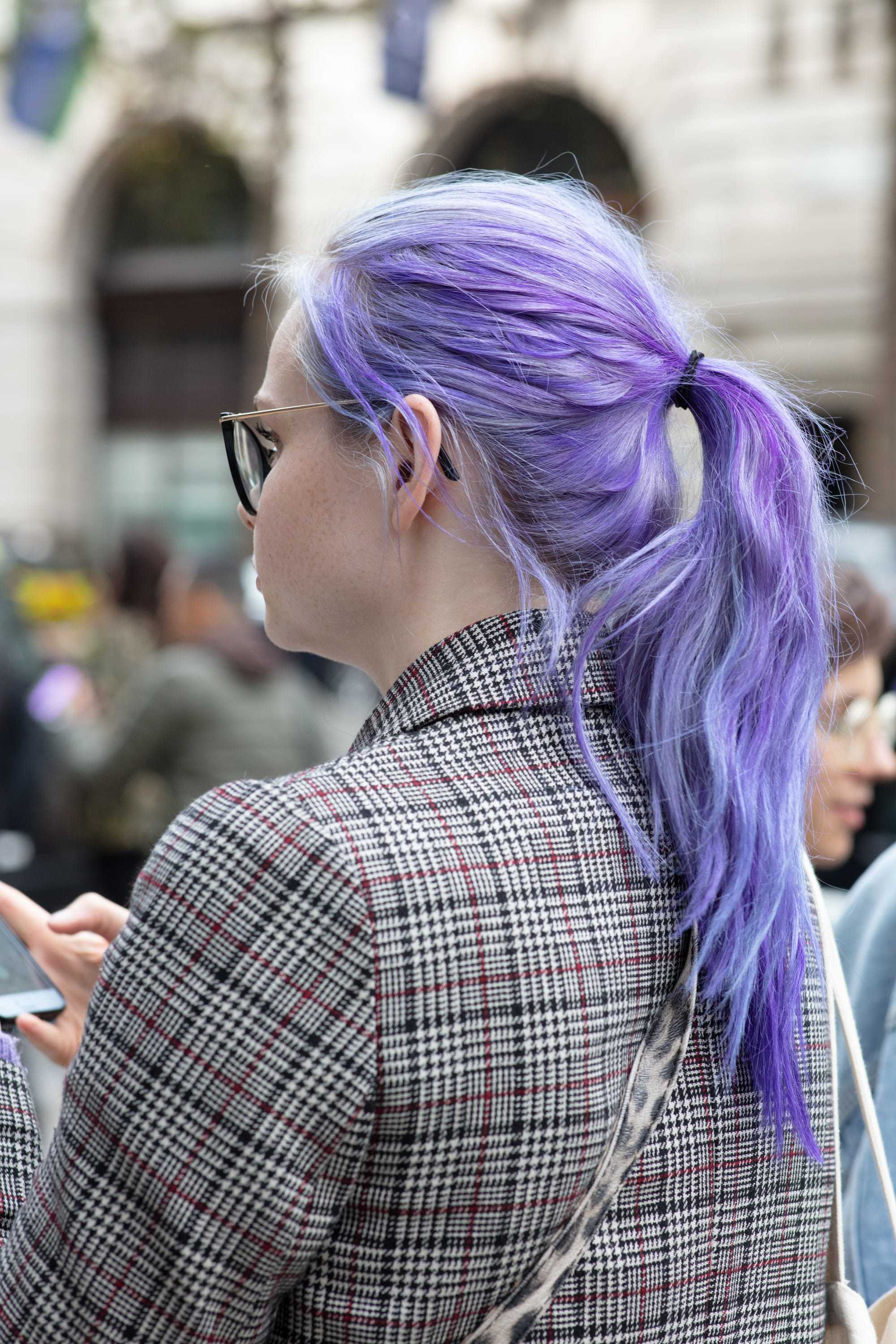 Washing hair after colouring: Rear view of women with long purple hair styled into a ponytail, wearing blazer and posing for an All Things Hair street style shot
