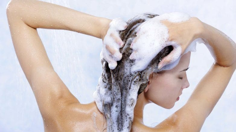 Washing hair after colouring brunette girl in shower with soapy hair